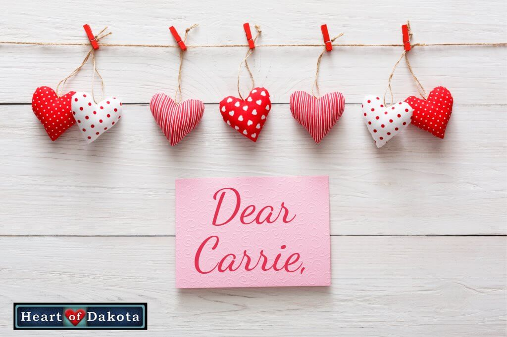 """Heart of Dakota Dear Carrie post - Picture of red, white, and pink cloth hearts on a clothesline, against a white wood background. Beneath the hearts, a pink post it note pinned to the wood reads """"Dear Carrie"""" in red, decorative handwriting"""
