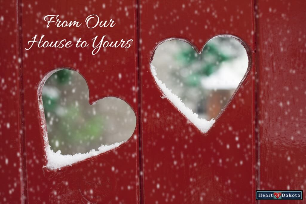 Heart of Dakota From Our House to Yours - Photo of a red painted fence with two heart shaped holes cut in it. Through the holes, a blurred snowy background is visible.