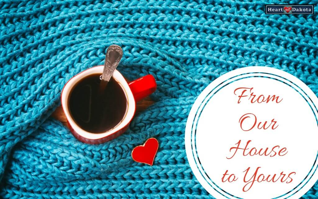 "Ceramic mug filled with coffee surrounded by a blue woolen scarf. A white text bubble on the right says ""From Our House to Yours."""