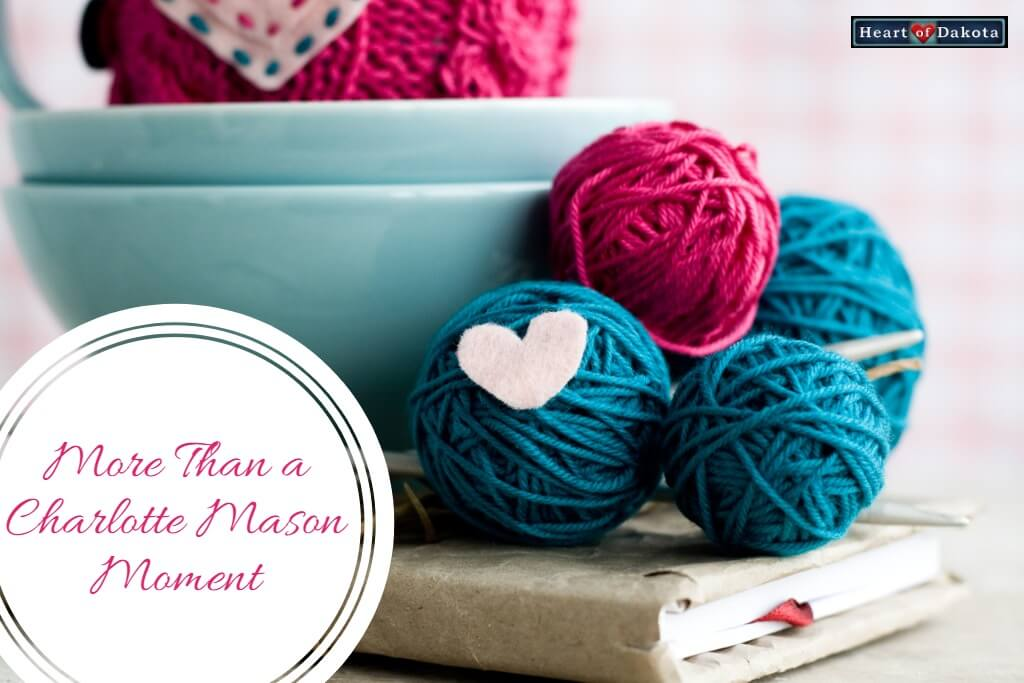 """Red and blue balls of yarn sitting atop a book on a tabletop. A white paper heart is pinned to one of the balls. To the left, inside a white circle, text reads: """"More Than a Charlotte Mason Moment."""""""