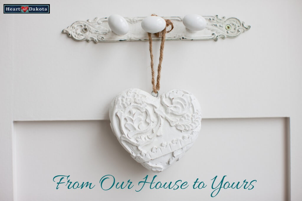 """White painted, decorative plaster heart hanging in front of a white door. Blue text near the bottom reads: """"From Our House to Yours."""""""
