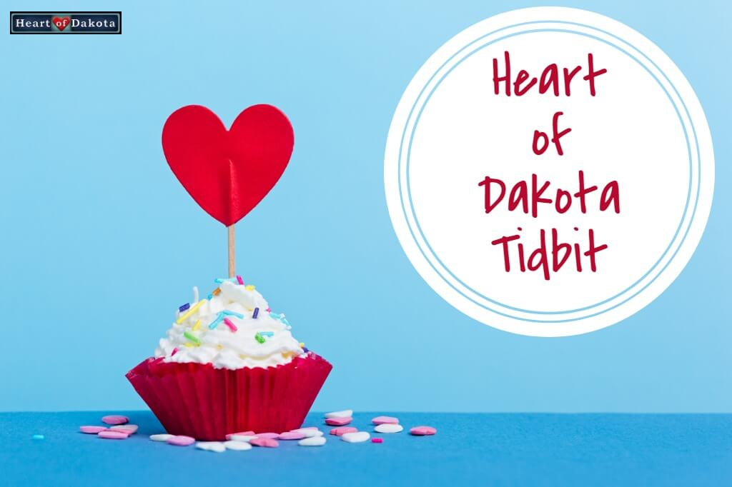"""Cupcake with multicolored sprinkles and a paper heart on a toothpick stuck on top. A white circle to the right reads """"Heart of Dakota Tidbit."""""""