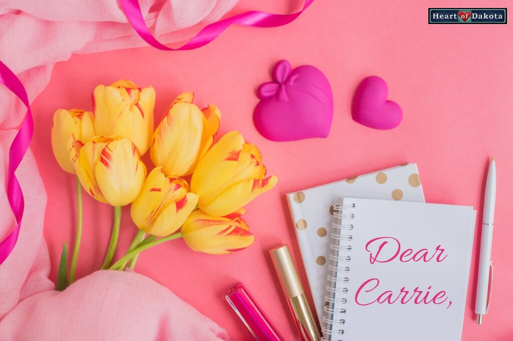 "Small white notebook lying on a pink background besides yellow tulips. On the notebook, pink script reads ""Dear Carrie."""