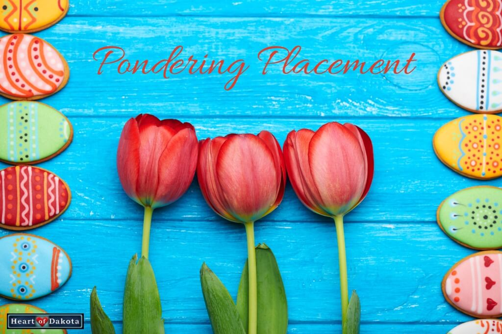 Red tulips against a bright blue wooden background. On either side, multicolored Easter egg cookies form a border.