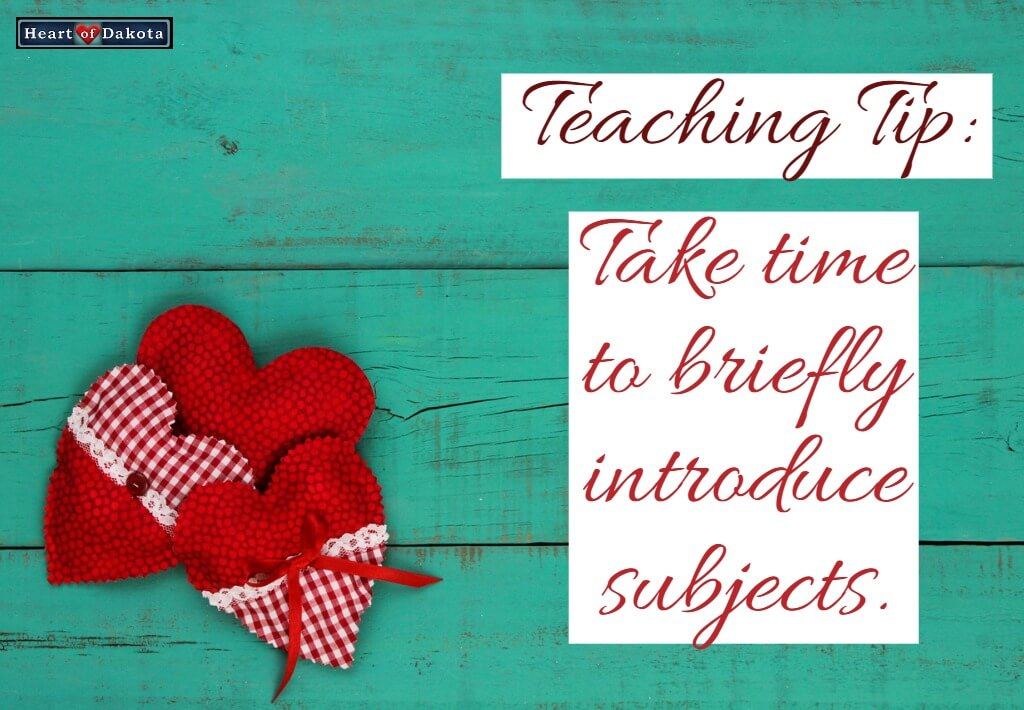 """Two plaid red hearts laying on a teal wood surface. A text placard to the right reads """"Take time to briefly introduce subjects."""""""