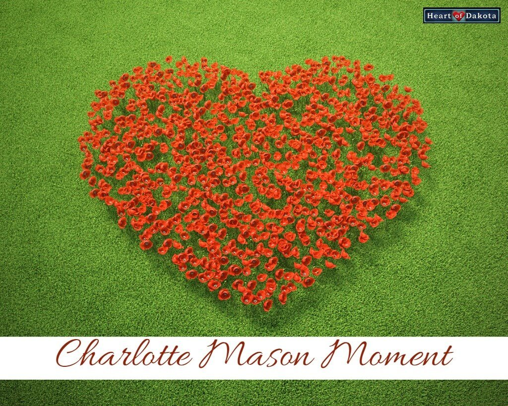 "Heart-shaped bed of red roses on green grass. Text on the bottom reads: ""Charlotte Mason Moment."""